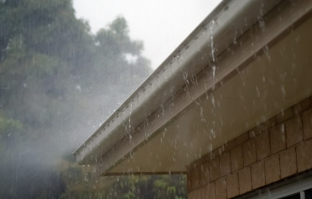 Metal Roof Gutter Overflowing From The Rain